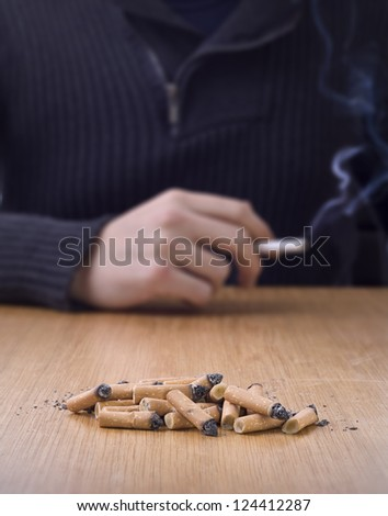 chain smoking, pile of cigarette butts on table with person smoking in background
