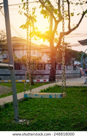 Chain swing in children playground with sunset background. - stock photo