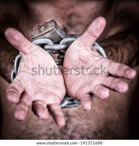 Chained hands gesturing to symbolize the need for freedom  (in a dark background) - stock photo