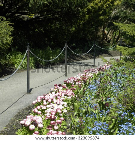 Chains and poles dividing a paved path in a garden  - stock photo