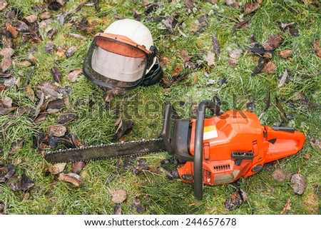 Chainsaw and helmet lying on the ground. - stock photo