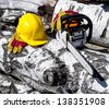 chainsaw and helmet on a background of trees felled - stock photo
