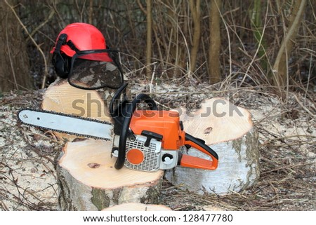 Chainsaw and protective safety equipment - stock photo