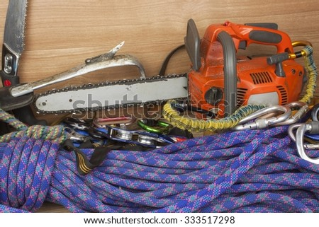 Chainsaw ready to work. Tools for trimming trees, utility arborists. Chainsaw, rope and carabiners to work lumberjack. Arborist - doctors trees - stock photo