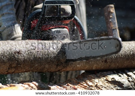 chainsaw to cut firewood - stock photo