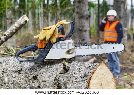 Chainsaw with gloves in background lumberjack talking on smart phone - stock photo