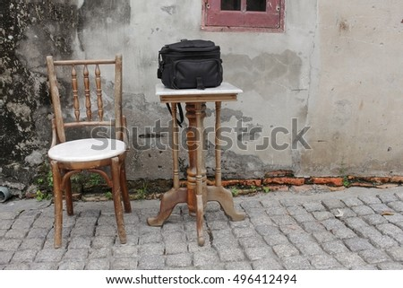 chair and black bag  on table ancient at The background is the old wall