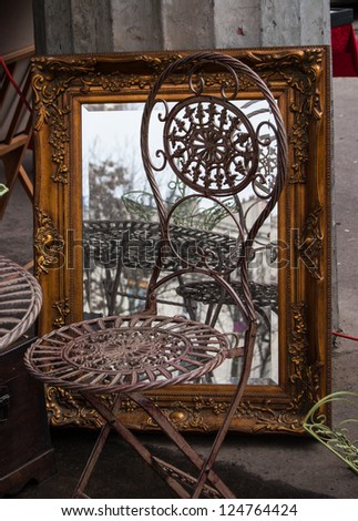 Chair and mirror in golden frame at flea market in Paris. Retro style postcard. - stock photo