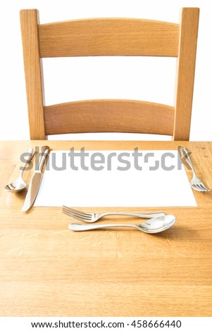 Chair and place setting and on a wooden table with knife, fork , soup spoon and desert cutlery - stock photo