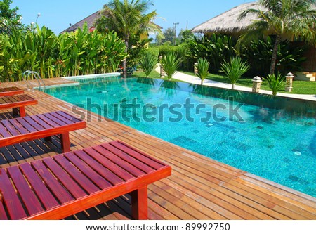 chair and swimming pool surrounded by  tropical plants