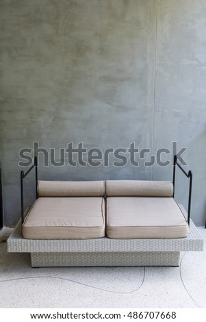 Chair in empty room against concrete wall