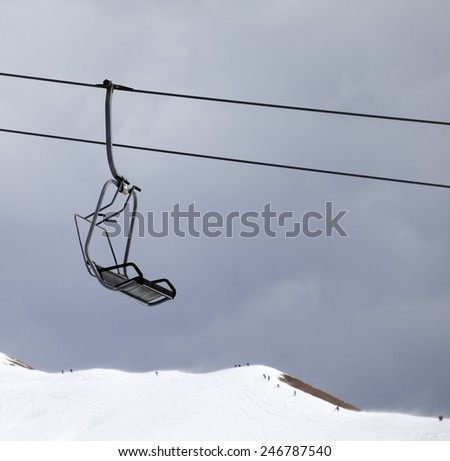 Chair lift and off-piste slope at gray windy day. Caucasus Mountains, Georgia, ski resort Gudauri. - stock photo