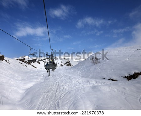 Chair-lift and off-piste slope in sun day. Caucasus Mountains, Georgia, ski resort Gudauri.  - stock photo