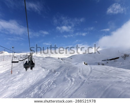 Chair-lift and off-piste slope in wind day. Caucasus Mountains, Georgia, ski resort Gudauri. - stock photo