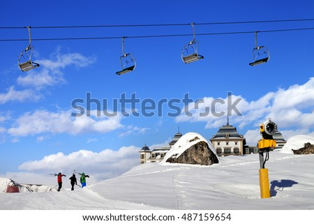 Chair-lift in blue sky and three skiers on ski slope at sun nice day. Greater Caucasus, Mount Shahdagh, Azerbaijan.