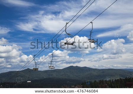 chair lift on a background of blue sky and clouds