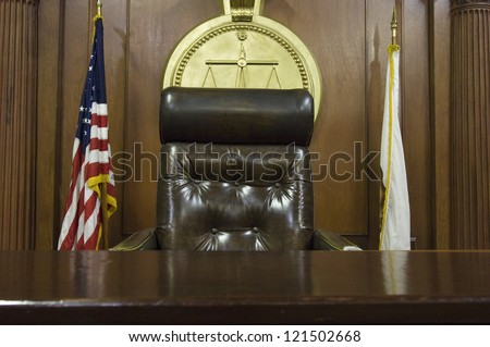 Chair of judge and flags in empty courtroom - stock photo
