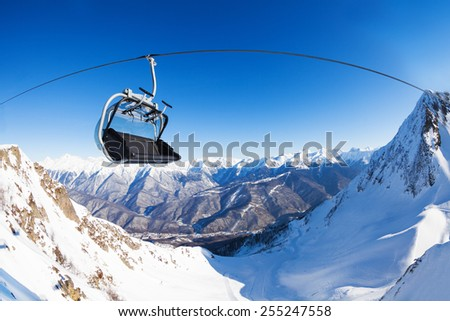 Chair on ski lift over mountain peaks panorama  - stock photo