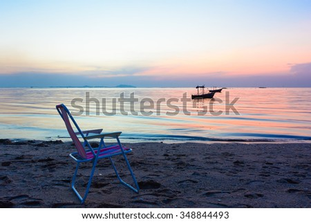 Chair on the beach in evening. Beach and sunset background