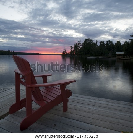 Chair on the dock at sunset in Lake of the Woods, Ontario - stock photo