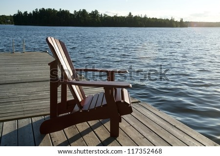 Chair on the dock overlooking the lake at Lake of the Woods, Ontario - stock photo
