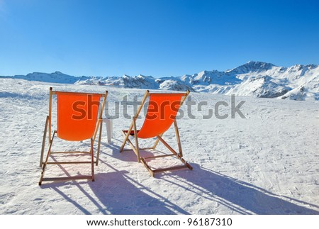 chair on top of mountain range at winter season sunny day with blue sky in background representing concept of relax - stock photo