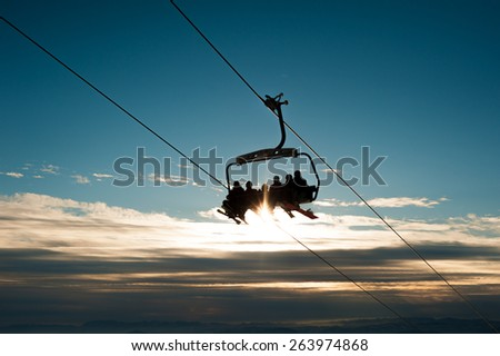 Chair ski lift with skiers over blue sky in the evening - stock photo