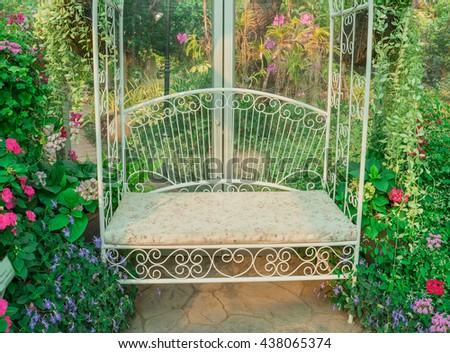 Chair. White chair. White bench. White chair in flower garden. Beautiful white chair in floral glass green garden with morning sun light