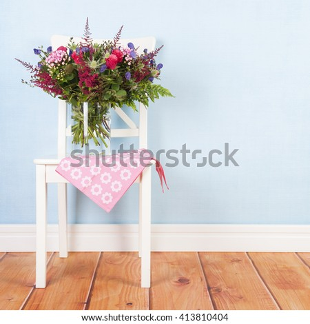 Chair with vase mixed bouquet flowers on blue background - stock photo