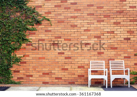 Chair wood with wall blick and tree plant on background. - stock photo