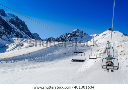 Chairlift on a ski resort. Beautiful winter landscape in the mountains and blue sky with clouds.