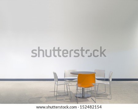 chairs and a table in front of a white wall with space to paste your own images - stock photo