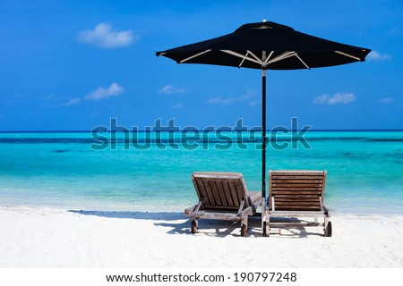 Chairs and black umbrella on a beautiful tropical beach at Maldives