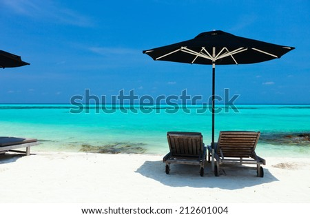 Chairs and black umbrella on a beautiful tropical beach at Maldives - stock photo