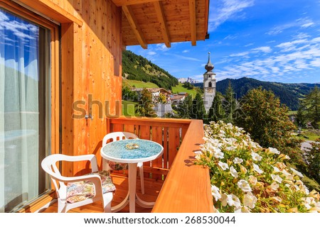 Chairs and table on terrace of alpine house with view of Colfosco village in Dolomites Mountains, Italy - stock photo