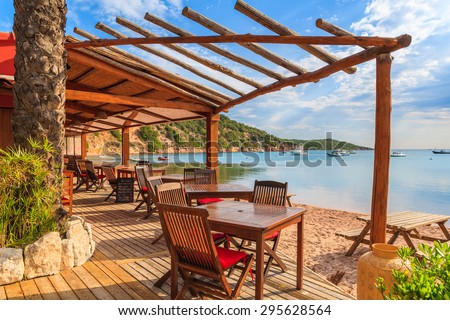 Chairs and tables in beach bar in Santa Manza bay, Corsica island, France - stock photo