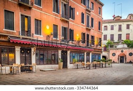 Chairs and tables in front of venetian cafe - stock photo