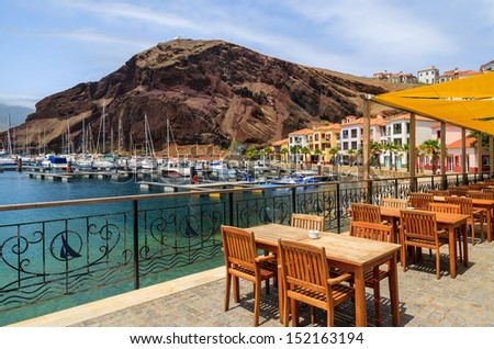 Chairs and tables of local restaurant in harbour with boats and yachts and colorful houses, Madeira island, Portugal  - stock photo