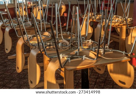 Chairs and tables stacked in a closed restaurant. - stock photo