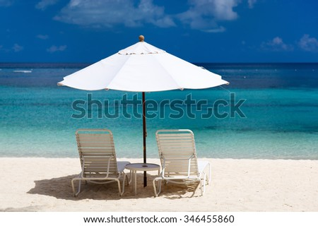 Chairs and umbrella on a beautiful tropical beach - stock photo