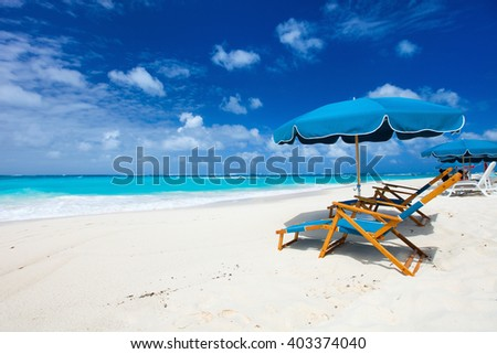 Chairs and umbrella on a beautiful tropical beach at Anguilla, Caribbean - stock photo