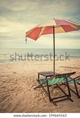 chairs and umbrella on the beach (retro style)
