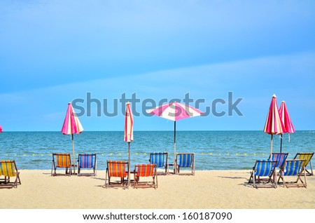 Chairs and umbrella on white sand beach. - stock photo