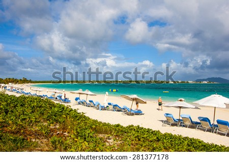 Chairs and umbrellas line the beautiful tropical beach in Anguilla Caribbean with turquoise waters as a backdrop and think cumulus clouds - stock photo