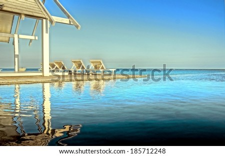 chairs by the beach with a fantastic swimming pool on a tropical destination - stock photo