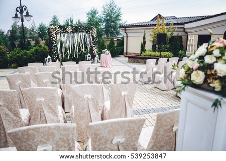 Chairs covered with beige cloth stand in rows before wedding altar