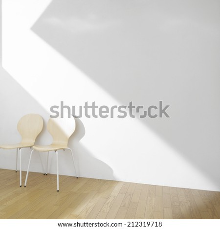 chairs in empty room with sunlight - stock photo