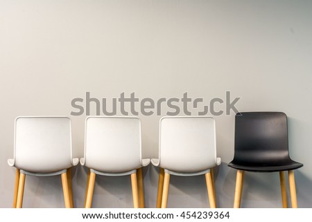 Chairs in modern design arranged in front of the gradient grey wall for interior or graphic backgrounds