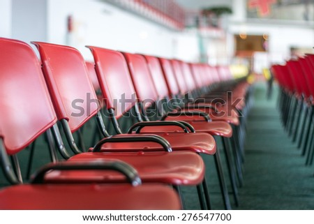 Chairs in sport centre, row of red seats - stock photo