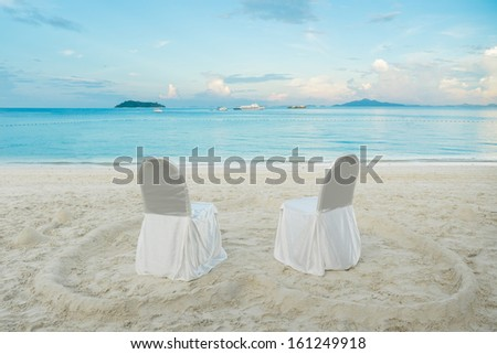 chairs in the heart shaped sand on the beach - stock photo